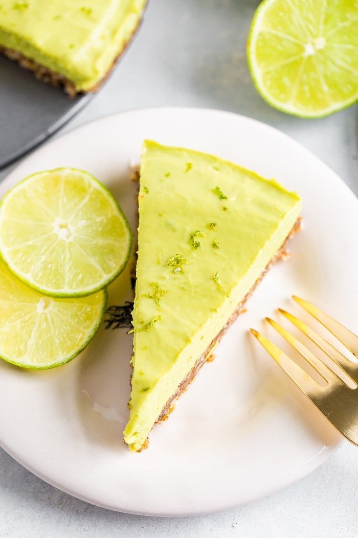 Slice of avocado lime tart on a plate with a gold fork and two slices of lime.