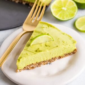 Slice of avocado lime tart on a plate with a fork and topped with lime zest and a lime slice.