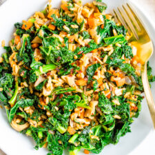 Bowl of sautéed kale, mushrooms and Spanish rice with a gold fork.