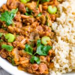 Plate of red beans and rice topped with fresh celery ad parsley.