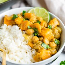 Bowl with half rice and half sweet potato chickpea curry topped with cilantro and lime.