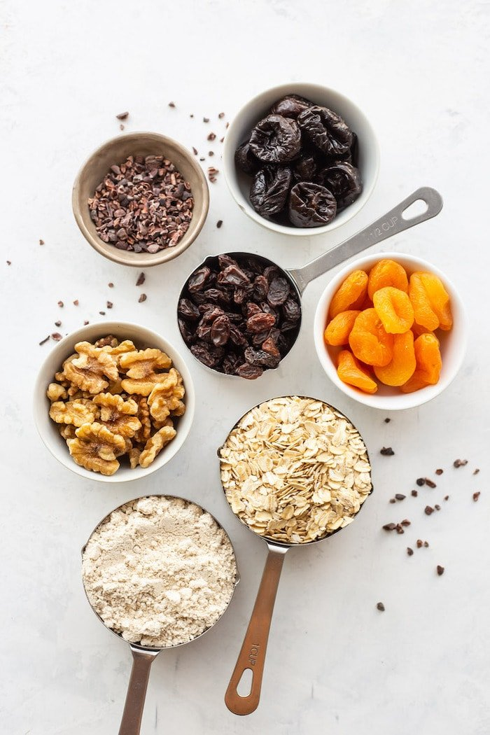 Ingredients to make fruit and nut bars in measuring cups, including oats, walnuts, and dried fruit.