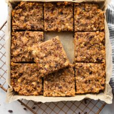 Square pan with fruit and nut bars cut into 9 slices. The middle square is sitting on top of the surrounding square pieces. The pan is sitting on a cooling rack.
