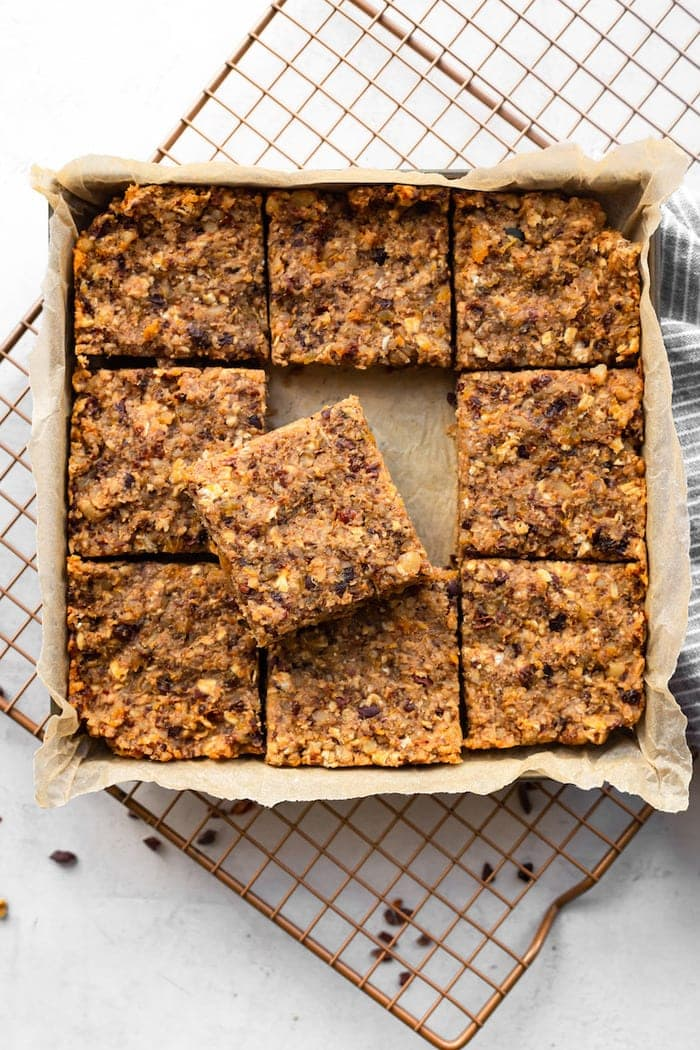 Square pan with fruit and nut bars cut into 9 slices.