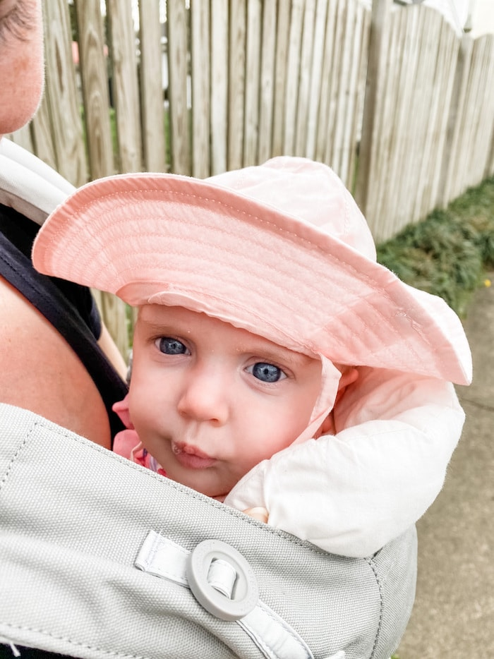 Baby girl wearing a sun hat in a Ergo 360 baby carrier