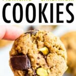 Hand holding an almond flour cookie with dark chocolate chunks and pistachios