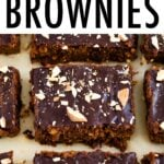 Sweet potato brownies on parchment paper topped with a chocolate ganache and chopped almonds.