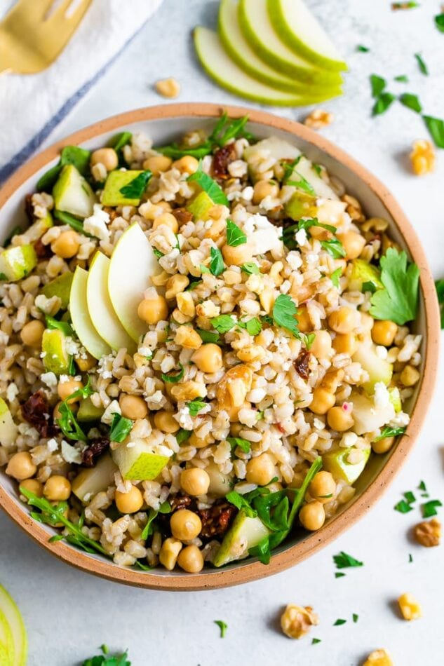 Bowl of barley salad with chickpeas and pear. Table is scattered with herbs and walnuts.