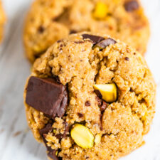 Two cookies studded with pistachios and dark chocolate chunks.