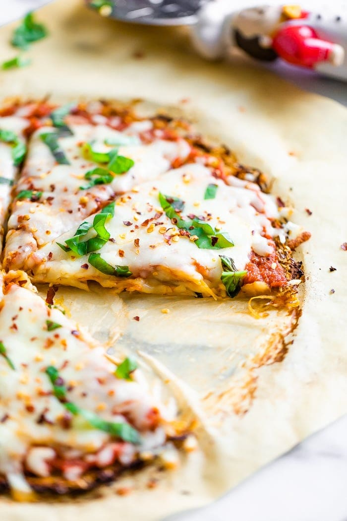 Spaghetti squash pizza crust pizza topped with fresh basil and cheese. A slice is cut out from the pizza.