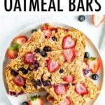 Oatmeal bars made with strawberries and blueberries stacked on a plate.