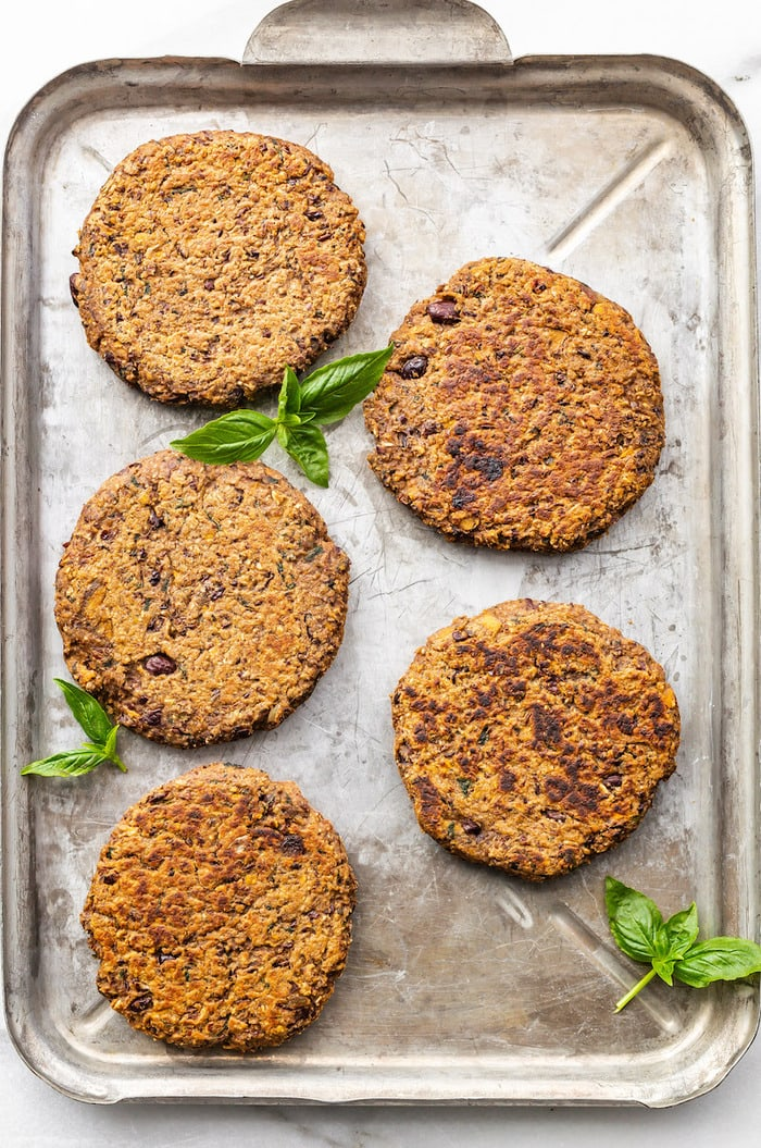 Five black bean sweet potato burgers on a baking sheet surrounded by basil leaves.