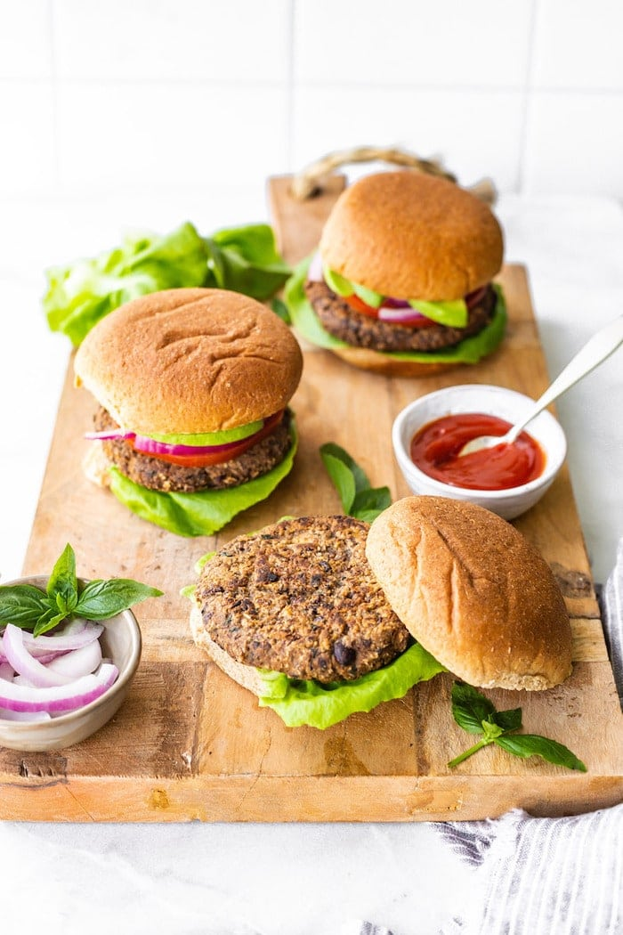 Three black bean sweet potato burgers on buns on a wood cutting board. A bowl of ketchup and onions are beside the burgers.