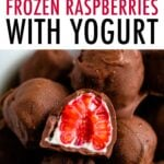 Bowl of chocolate covered frozen raspberries with yogurt. One raspberry is cut in half.