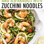 White sauté pan with zucchini noodles, asparagus and shrimp topped with red pepper flakes.