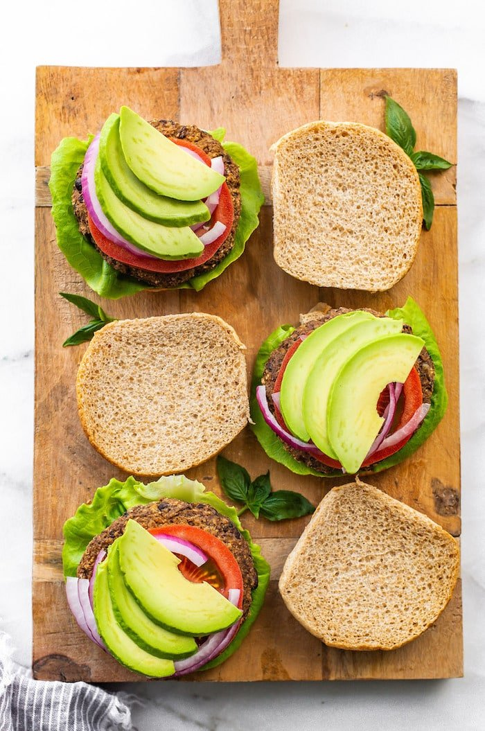 Three sweet potato black bean burgers on a wood board with the top bun off. Burgers are topped with tomatoes, onion, lettuce and avocado,