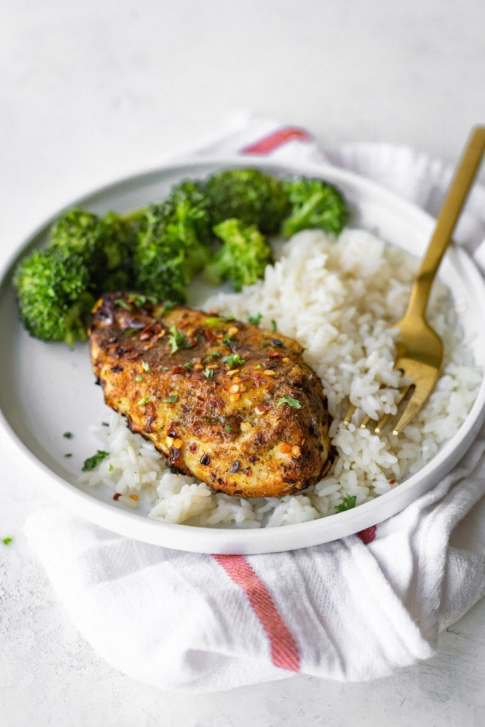 Grilled curry chicken on a plate with rice and broccoli.