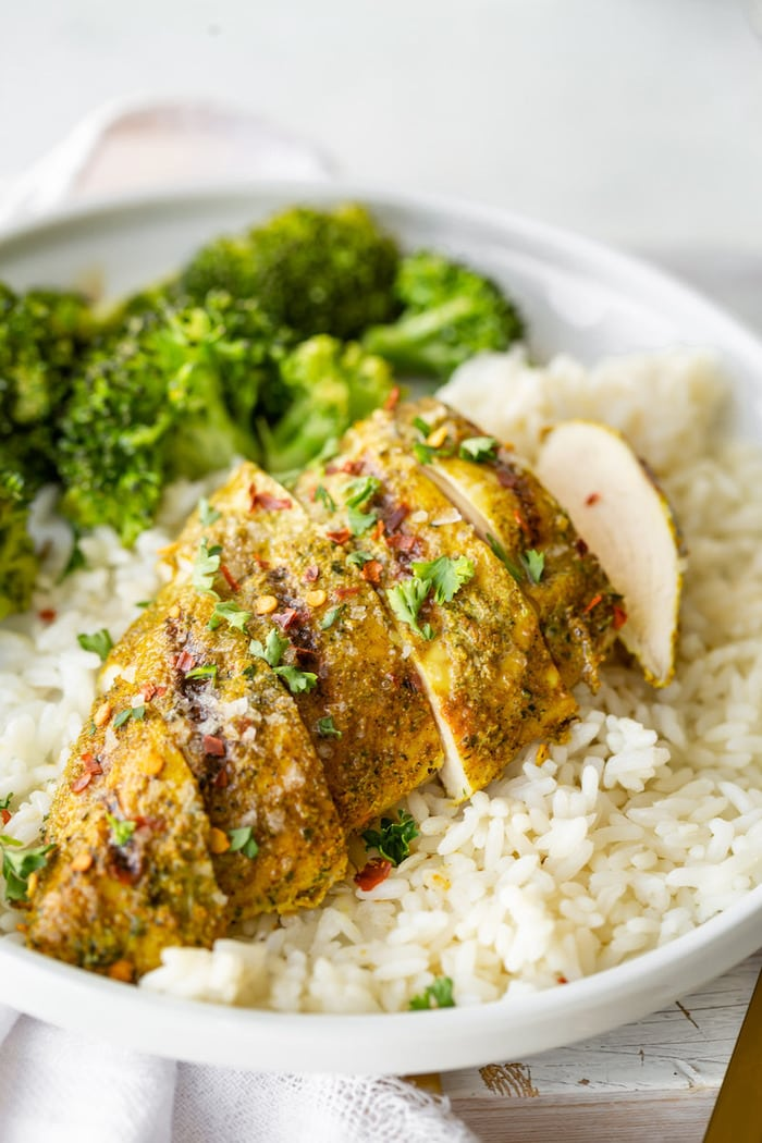 Sliced curry rub chicken breast topped with cilantro and red pepper flakes. Chicken is served over a bed of rice and next to broccoli.