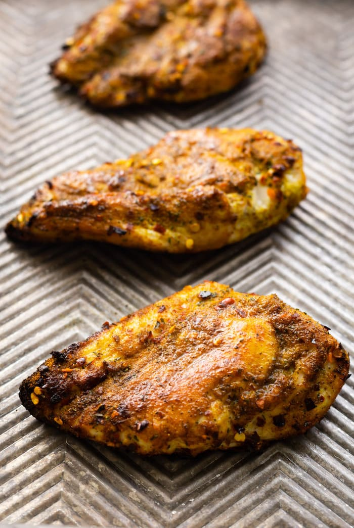Three curry rubbed chicken breasts on a cookie sheet.