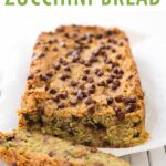Loaf of chocolate chip zucchini bread on a cloth and cooking rack with one slice cut.