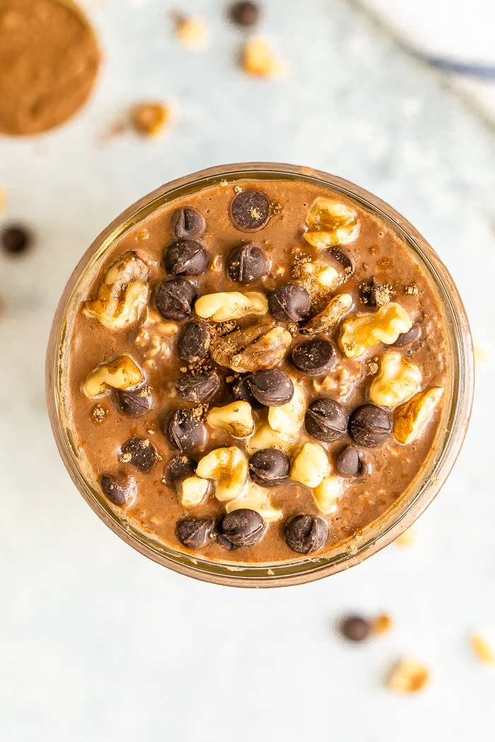 Overhead shot of chocolate brownie batter overnight oats in a mason jar. Topped with walnuts and chocolate chips.