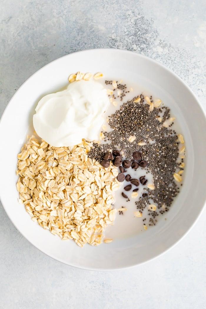 Ingredientes para a aveia durante a noite em pedaços de chocolate em uma tigela branca antes de misturar.