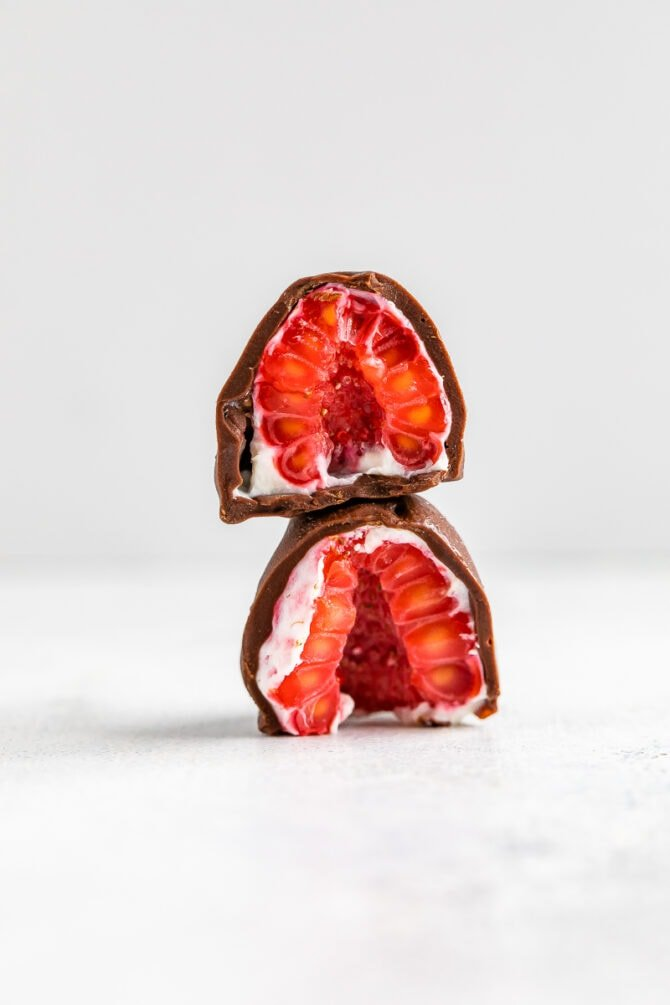 A chocolate covered and yogurt dipped frozen raspberry cut in half and stacked on top of each other.