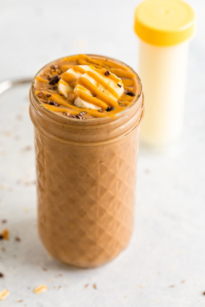 Jar filled with a chocolate smoothie topped with cacao nibs, banana slices and a peanut butter drizzle.