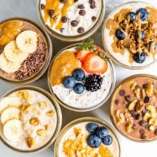 Overhead shot with 7 jars of overnight oats, each with different toppings.