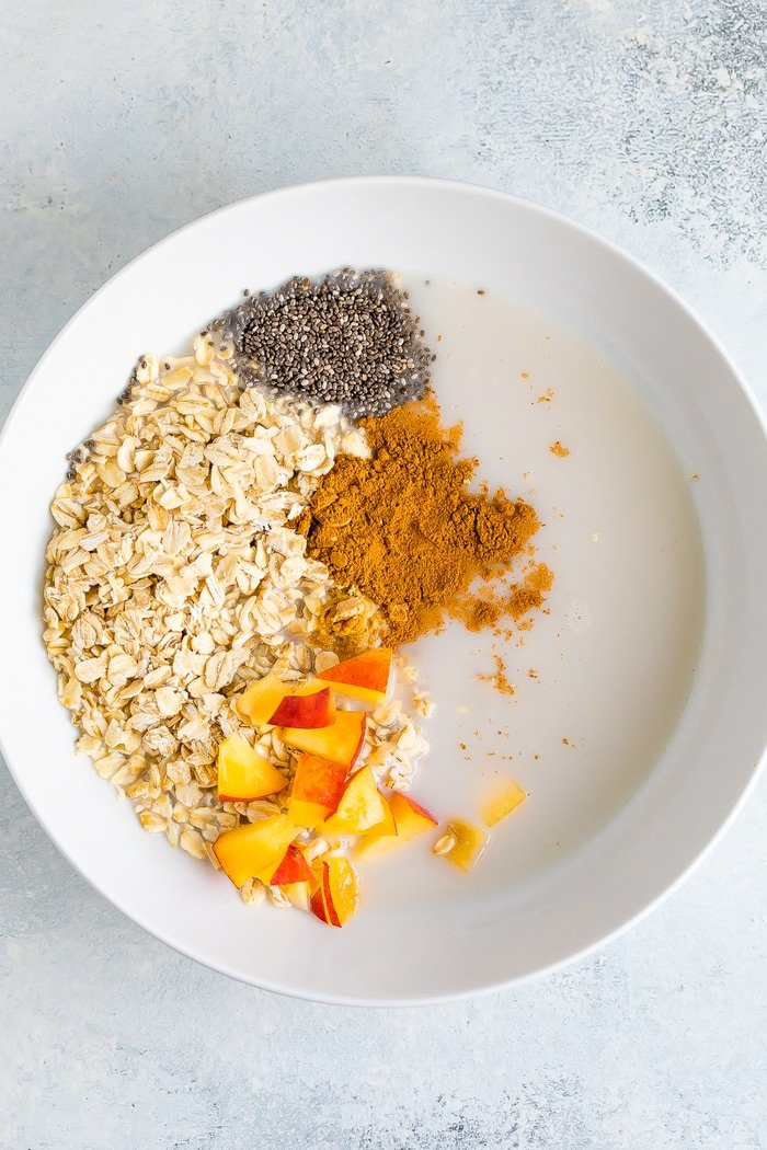 Ingredients for peach overnight oats in a white bowl before mixing.