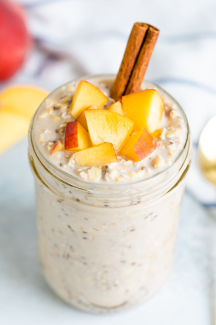 Peach overnight oats in a mason jar with fresh chopped peaches on top and a cinnamon stick.