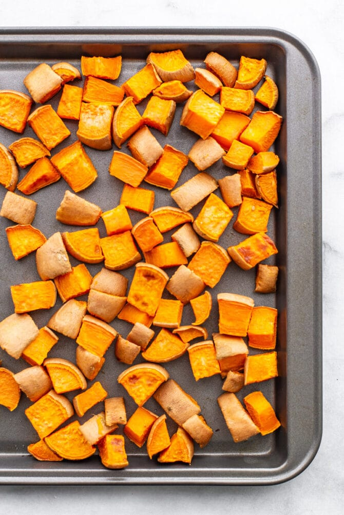 Sweet potato chunks roasted on a sheet pan.