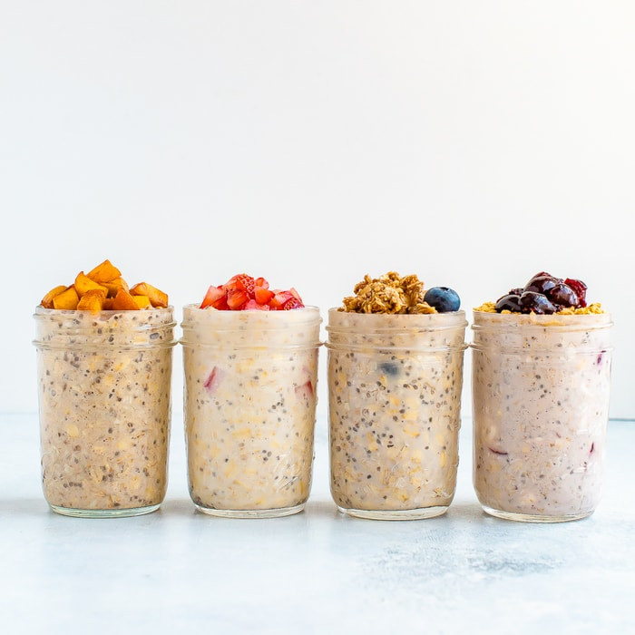Straight on shot with four mason jars with different overnight oat flavors: cherry cheesecake, peach pie, strawberry and blueberry crumble