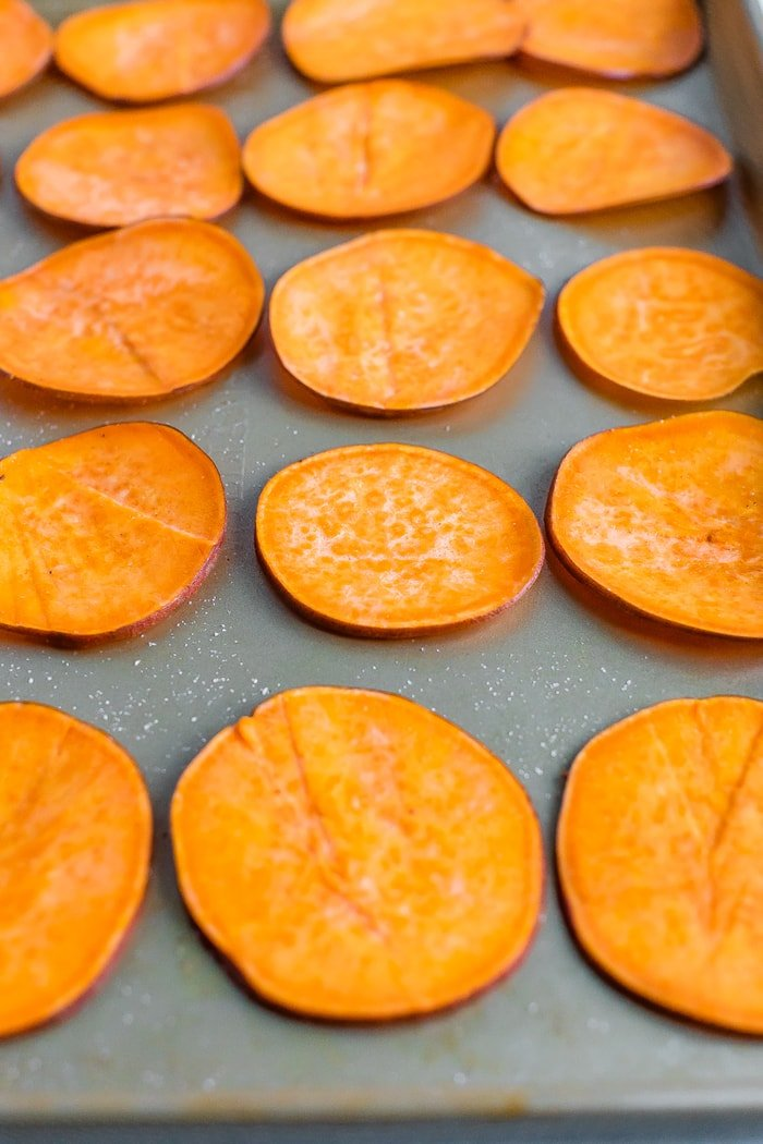 Thin slices of sweet potatoes on a cookie sheet.