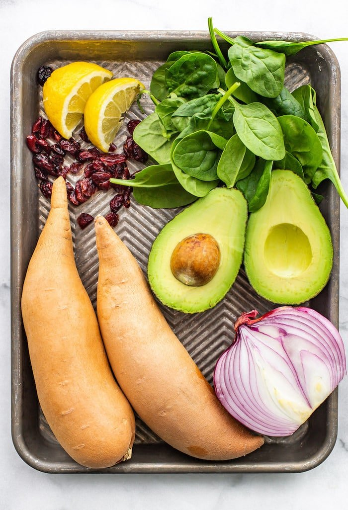 Lemon, cranberries, spinach, avocado, sweet potatoes and red onion on a sheet pan.