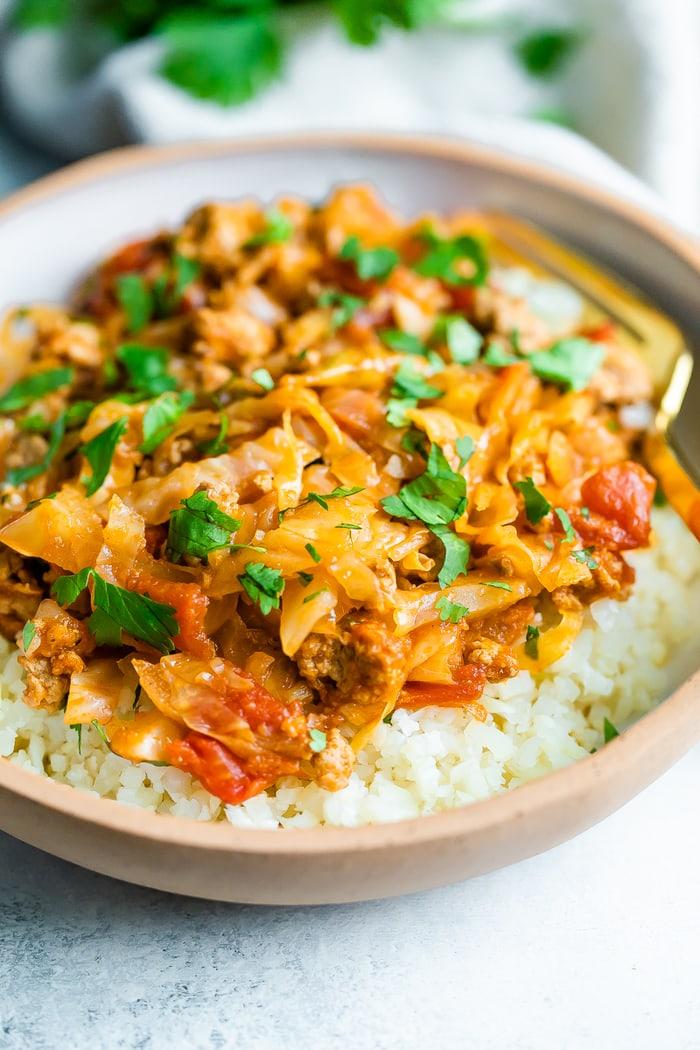 Feche acima da imagem da bacia do rolo de repolho não recheada. Repolho e peru são misturados com molho de tomate e servidos com arroz. A comida é servida em uma tigela de cerâmica com um garfo de ouro descansando dentro da tigela.