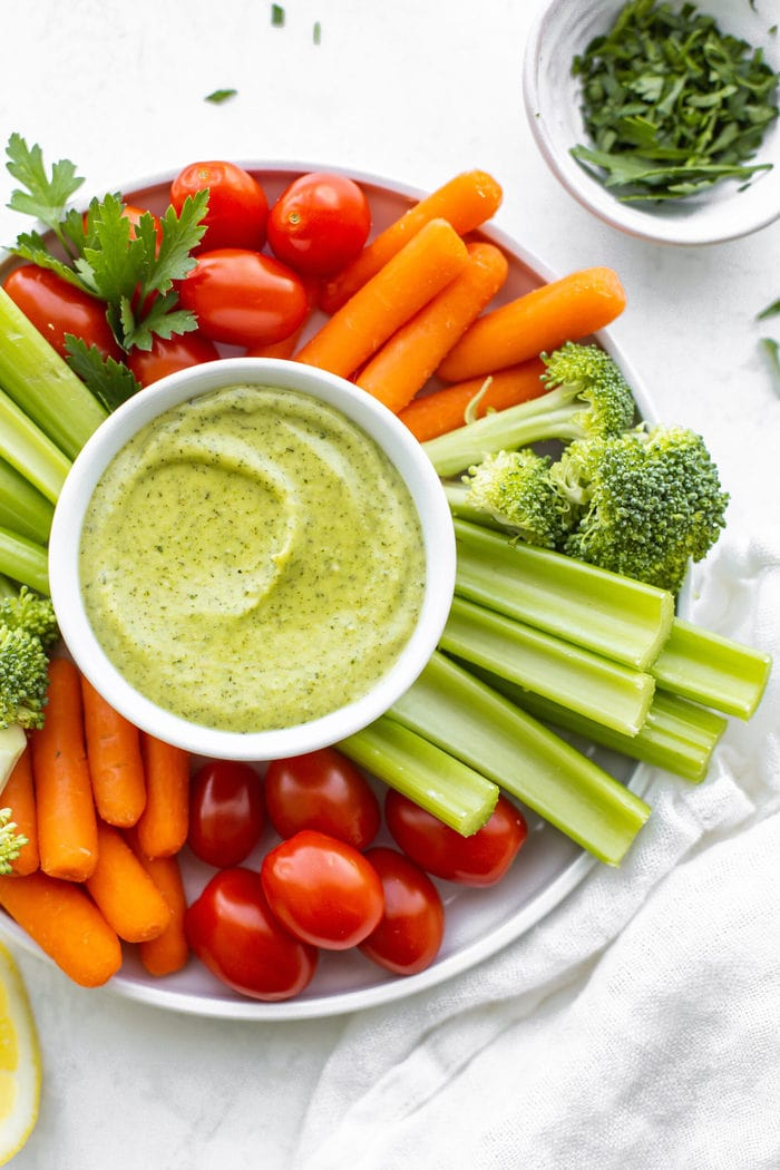 Veggie tray platter with tomatoes, carrots, celery, broccoli and avocado ranch dip in a white bowl.