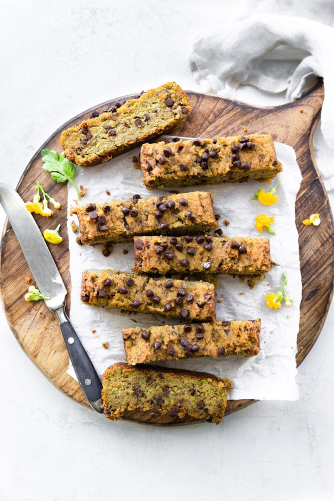 Slices of zucchini bread on a wooden cutting board surrounded by yellow flowers, a cloth napkin and a knife.
