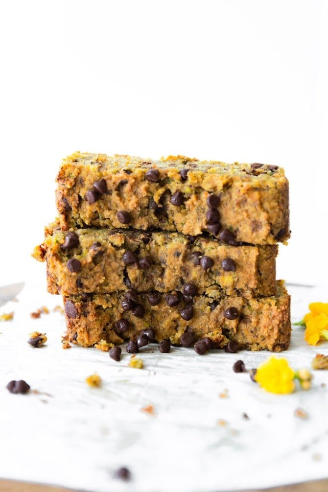 Three slices of chocolate chip zucchini bread stacked on top of each other. Chocolate chips and yellow flowers are scattered around.