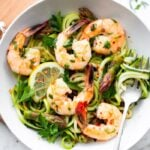 Bowl with zucchini noodles, asparagus and shrimp garnished with lemon and red pepper flakes.