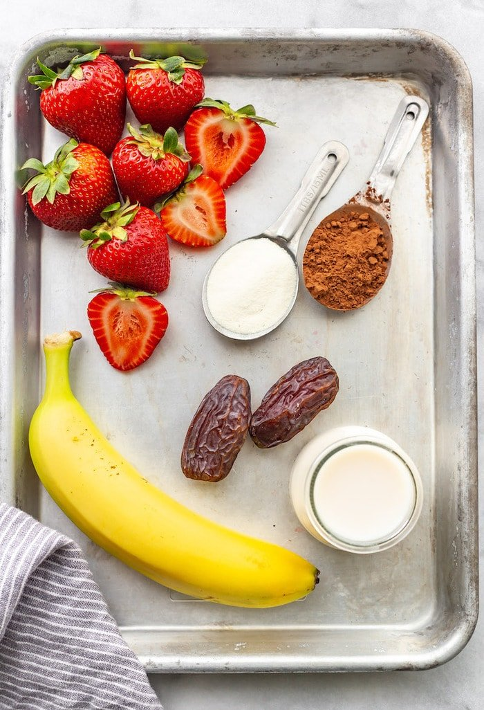 Ingredients to make a chocolate strawberry smoothie on a cookie sheet. Ingredients on the cookie sheet are strawberries, protein powder, cocoa powder, dates, almond milk and banana.