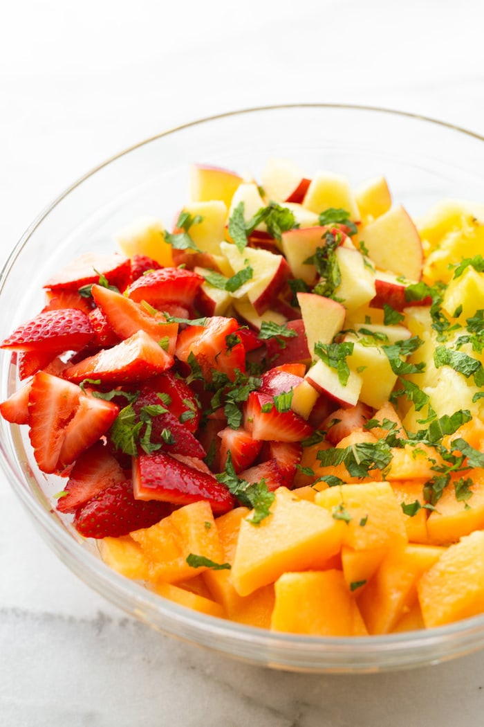 Glass mixing bowl with chopped strawberries, melon, apples, pineapple and fresh mint.