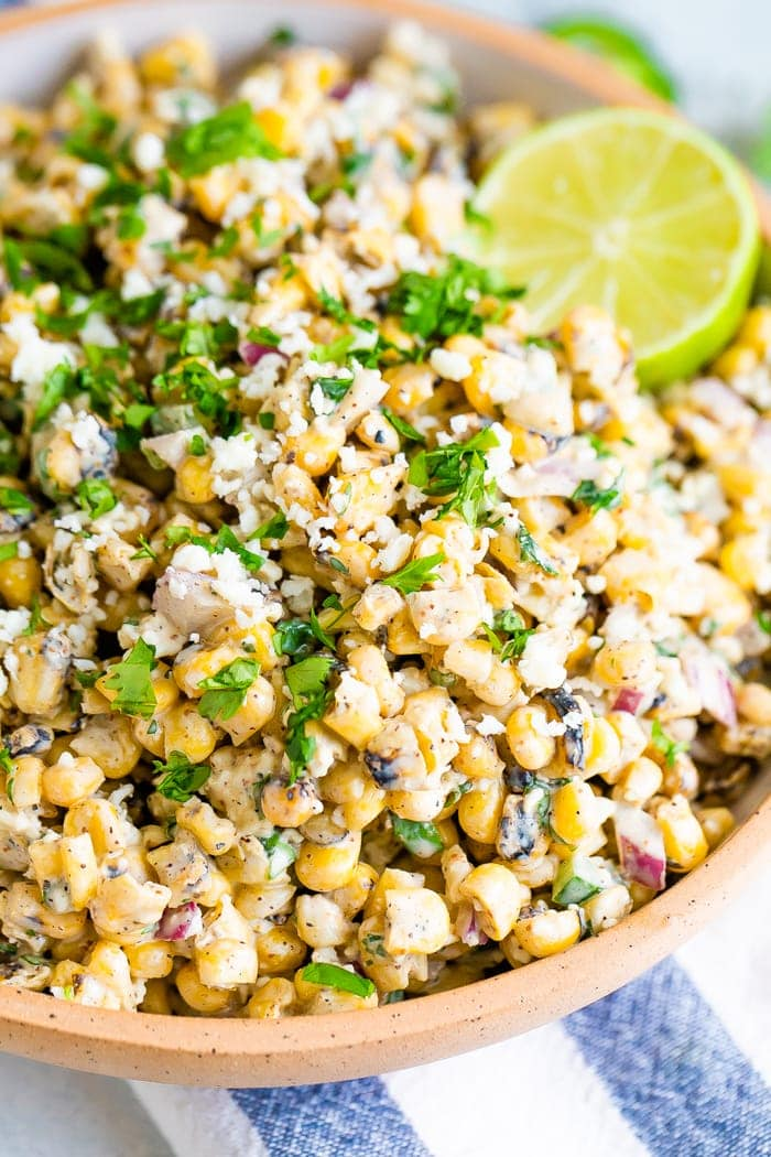 Close up photo of Mexican street corn salad in a bowl garnished with cilantro and lime. Corn is tossed in a light creamy dressing.