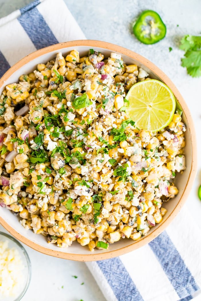 Bird's eye view photo of a bowl of Mexican Street Corn Salad topped with lime and fresh cilantro. Bowl is resting on a striped napkin.