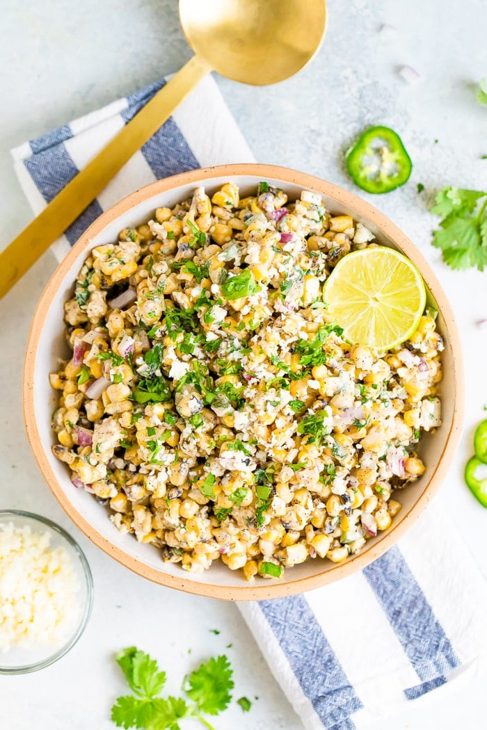 Bird's eye view photo of a bowl of Mexican Street Corn Salad topped with lime and fresh cilantro. Bowl is resting on a striped napkin and next to a gold spoon and bowl of cheese.