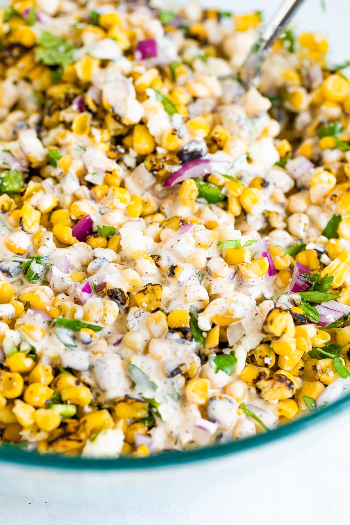 Close up photo of Mexican street corn salad in a bowl. Corn, red onion and cilantro drizzled with a creamy dressing.