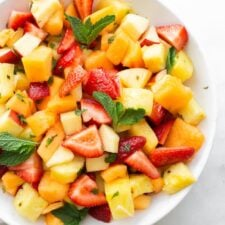 White bowl with fruit salad including strawberries, pineapple, melon, apples and mint.