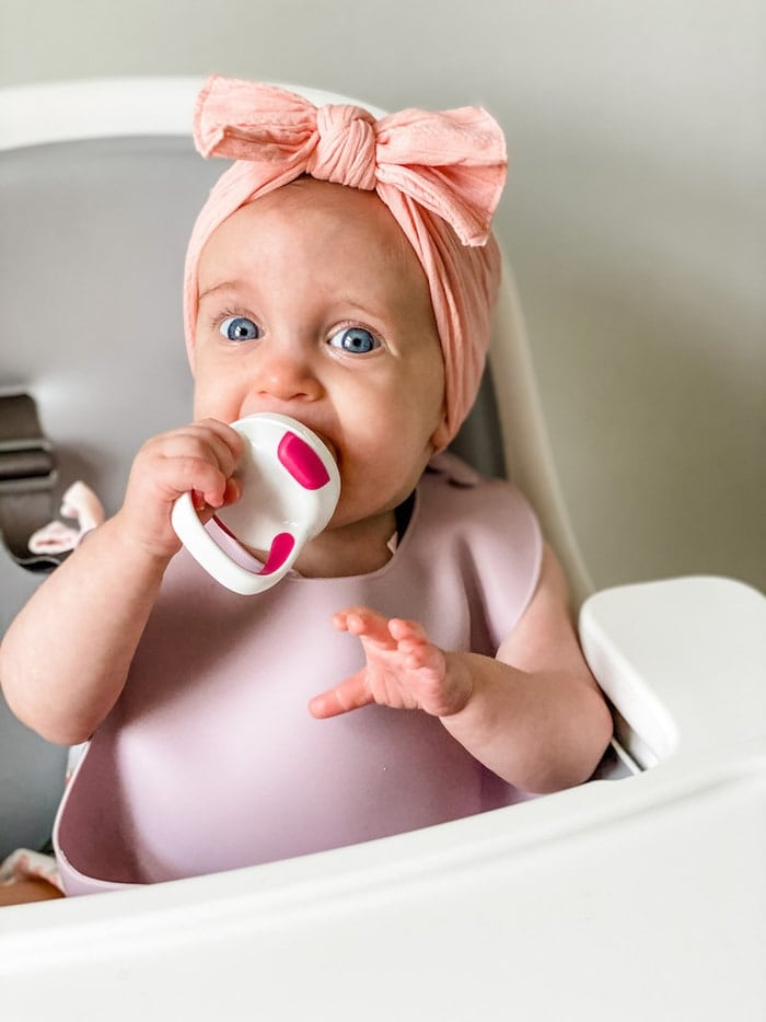 Baby girl with a bow using OXO self feeder