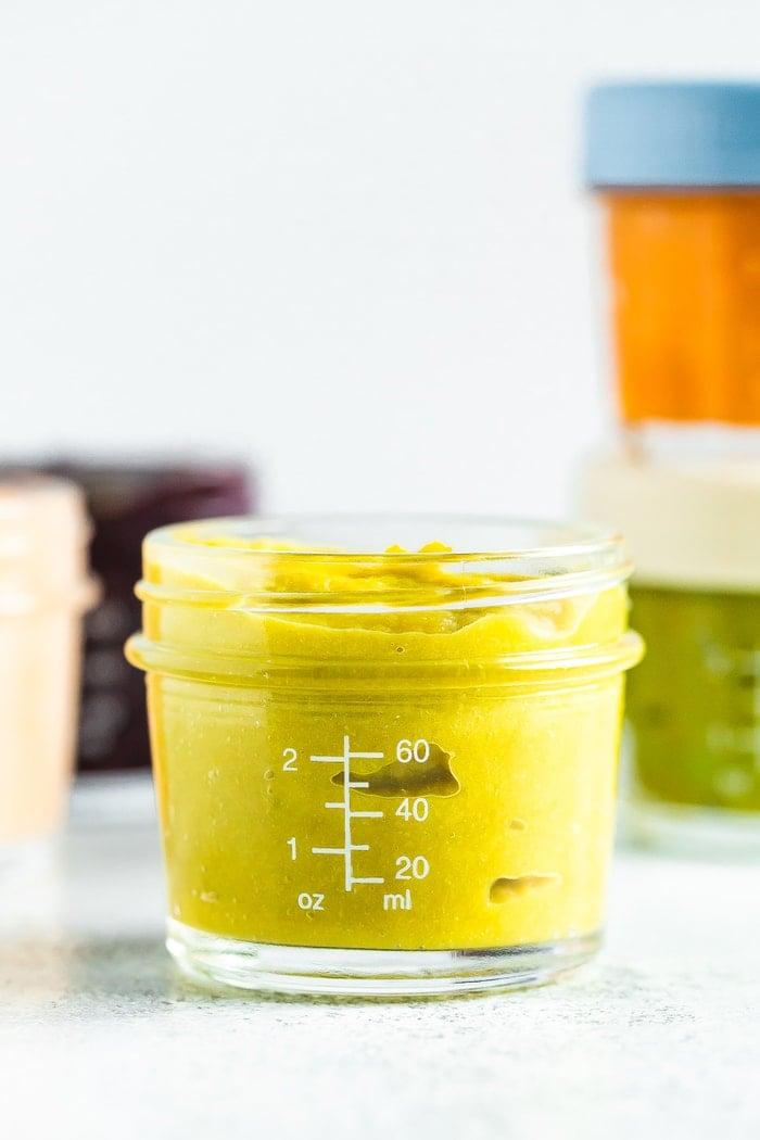 Asparagus apple baby food in a 4 oz baby food jar.