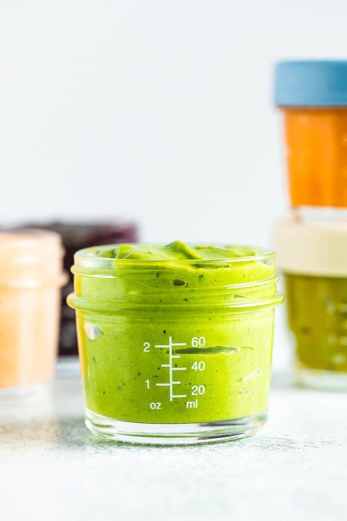 Avocado peach pineapple kale baby food in a 4 oz baby food jar.